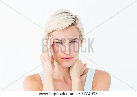 Blonde woman suffering from headache and neck ache on white background