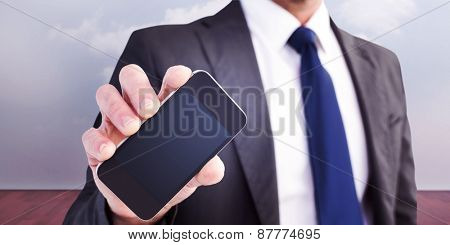 Businessman showing his smartphone screen against clouds in a room