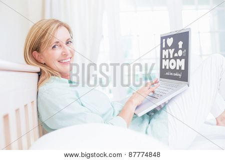 mothers day greeting against happy woman using laptop in her bed