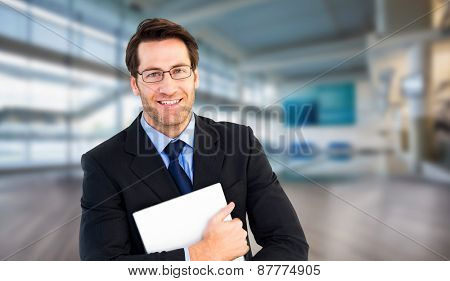 Smiling businessman holding his laptop looking at camera against fitness studio