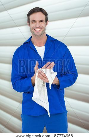 Confident mechanic wiping hand with napkin against grey shutters