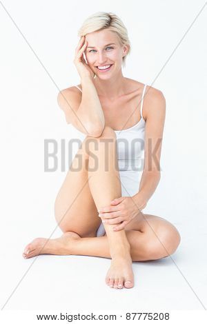 Gorgeous blonde sitting on the floor smiling at camera on white background
