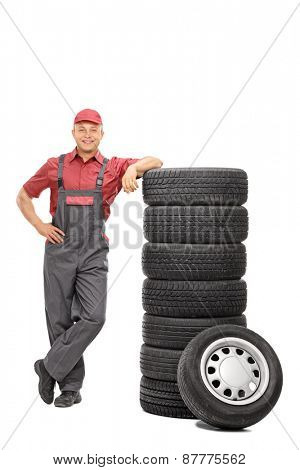 Full length portrait of a handsome young male mechanic leaning on a stack of tires isolated on white background