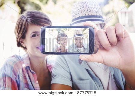 Hand holding smartphone showing against happy couple enjoying coffee together