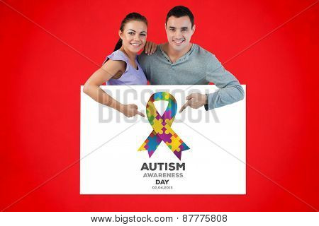 Young couple pointing at advertisement below them against red background