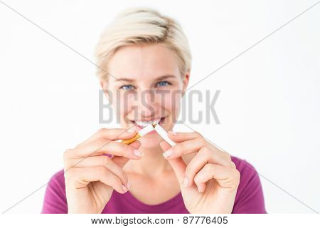 Pretty blonde breaking cigarette on white background