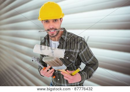 Manual worker holding various tools against grey shutters