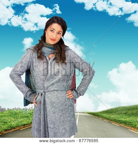 Serious pretty brunette wearing winter clothes posing against road leading out to the horizon