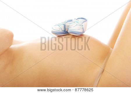 Small shoes for the unborn on the pregnant belly