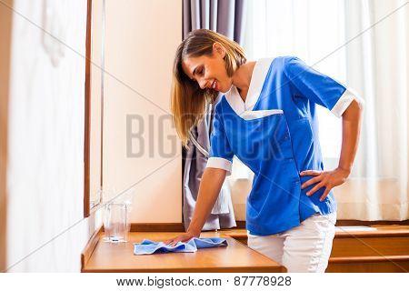 Hotel maid dusting