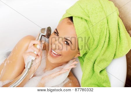 Spa woman having fun with showerhead.
