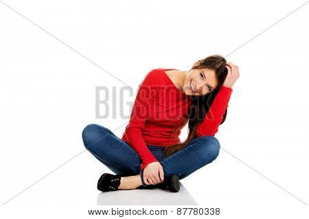Student woman sitting cross legged on the floor.