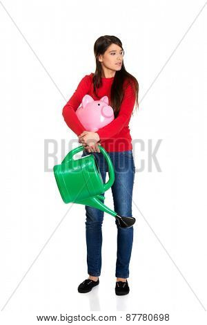Young woman holding a watering can and piggybank.