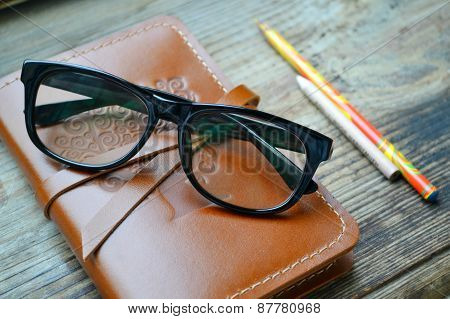 An old notebook in leather cover with pencils and glasses on wooden table