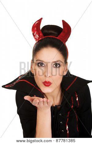 Beautiful woman in devil carnival costume blowing a kiss.