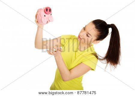 Sad teenage woman shaking piggybank for coins.