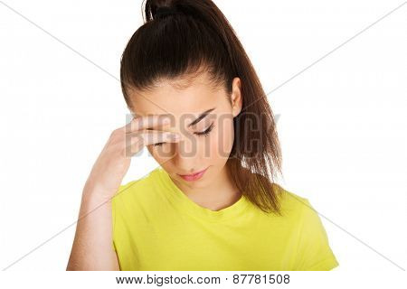 Teen woman with a headache holding head.