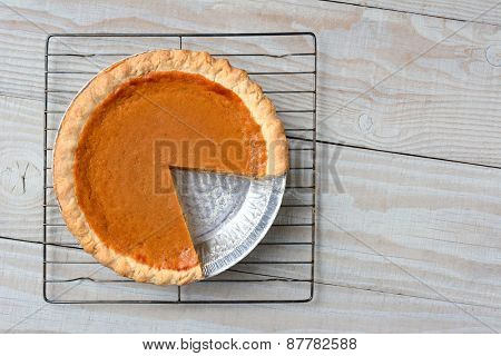 Overhead shot of a pumpkin pie with a slice cut out on a cooling rack. Horizontal format on a rustic white kitchen table.