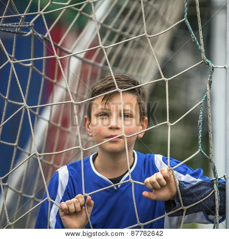 Little football player behind the football goal.