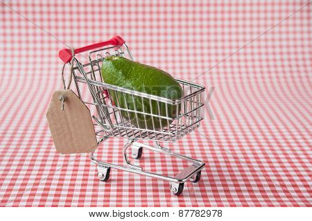 Ripe avocado in tiny shopping cart with blank price tag