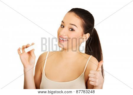 Woman with pregnancy test and thumbs up.