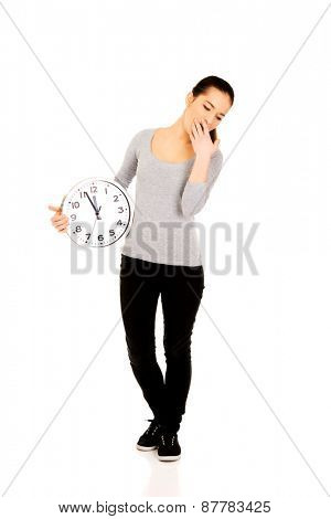 Tired yawning woman with a clock.