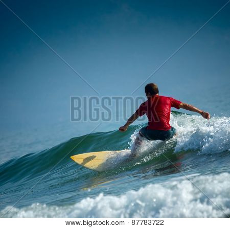 Surfer riding the wave on the short board at sunny day