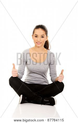 Young woman sitting cross legged with thumbs up.