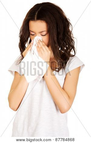 Unhealthy african teen sneezing to tissue.