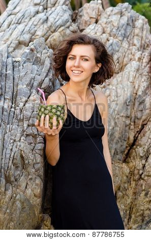 Woman drinks a cocktail from fresh pineapple