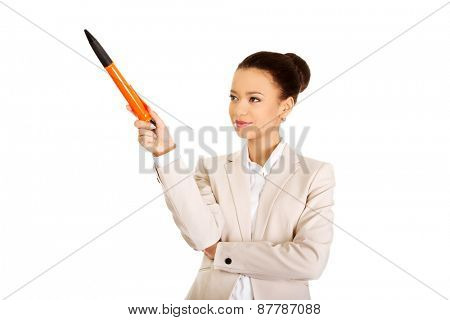 African businesswoman pointing up with big pen.