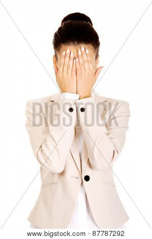 African businesswoman covering face with hands.