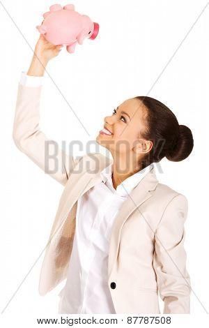 African business woman shaking piggybank.