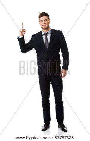 Happy handsome businessman points his finger up.