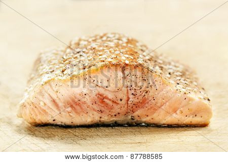 Salmon fillet with sesame seeds.  Side view, on wooden board.