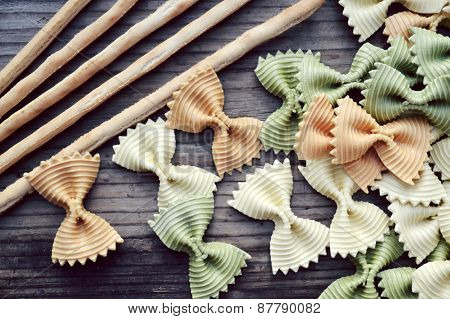 Uncooked butterfly shaped colorful pasta farfalle with breadsticks on wooden table
