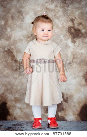 Adorable Little Girl With Blond Hair And Plump Cheeks Wearing Stylish Beige Dress And Red Shoes