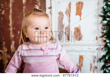 Cute Blond Little Girl With Big Grey Eyes And Plump Cheeks With Pursed Lips. Studio Portrait