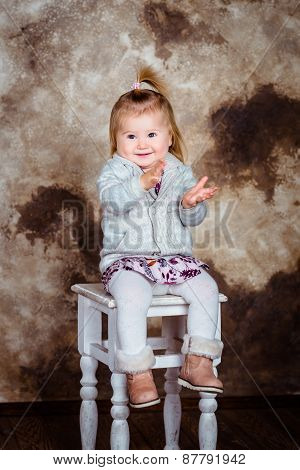 Adorable Little Girl With Blond Hair Sitting On Chair, Laughing And Clapping Her Hands