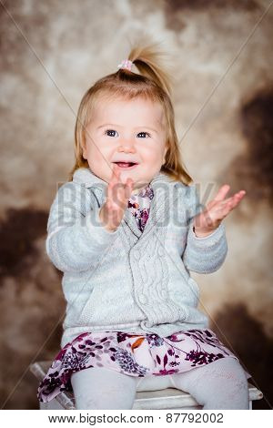 Pretty Little Girl With Blond Hair Sitting On Chair, Laughing And Clapping Her Hands