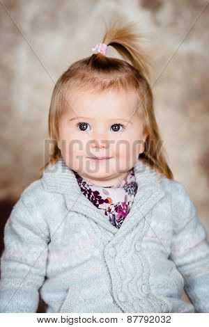 Close-up Studio Portrait Of Sweet Little Girl With Blond Hair And Plump Cheeks