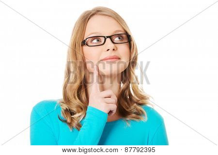 Happy pensive teenage woman with finger on cheek