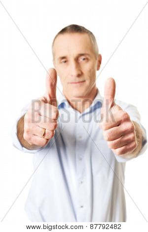Mature man with thumbs up gesture.