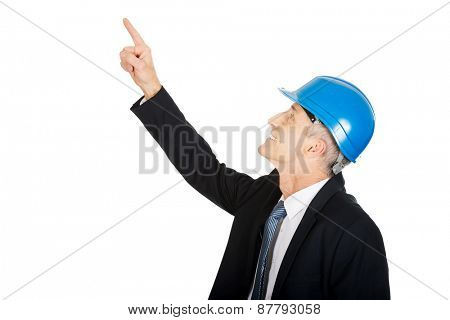 Mature businessman engineer with hard hat pointing up.