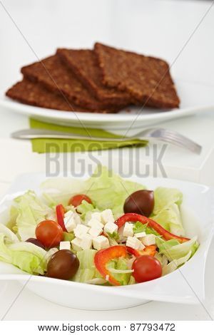 Fresh green salad in a plate and slices of brown bread placed on white tabletop.