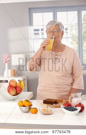 Granny drinking orange juice in the morning at home while preparing healthy breakfast.