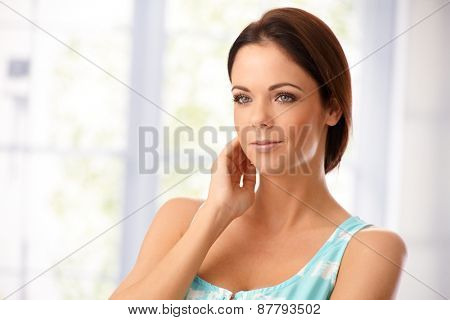 Portrait of attractive young woman looking away. Hand touching face.
