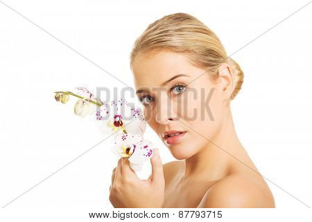 Beautiful spa woman with an orchid flower.