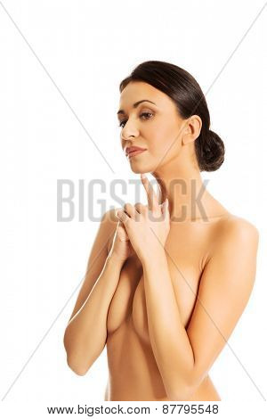 Pensive topless woman touching chin with a finger.