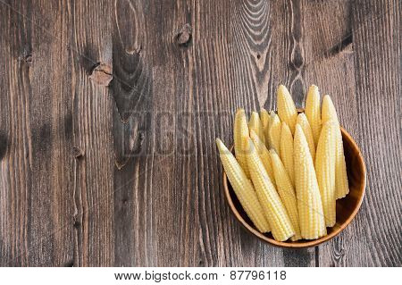 Small corn ears on wooden background